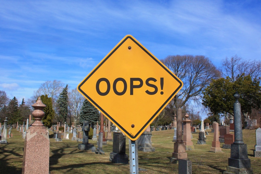 "branding fails. Yellow road sign that reads ""oops"" in front of a cemetary"