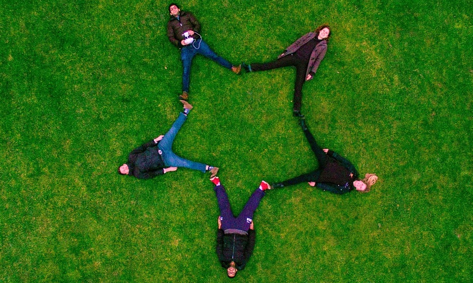 creating Company culture part 2. five employees laying in a field with their feet touching to form a star.